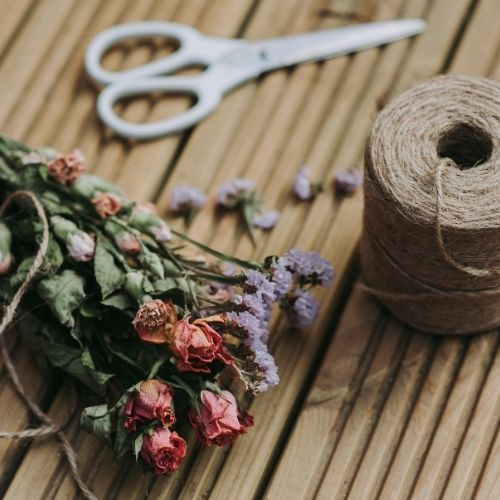 create an easy christmas gift with scissors, stalks of dried flowers and a spool of twine