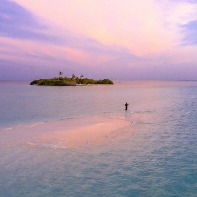 a person walking in the ocean at sunset towards an island