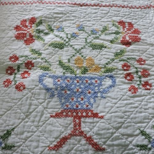 the lost art of handcrafting - a bed spread done in with a printed cross-stitch
