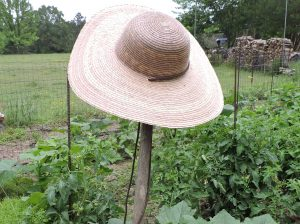 Straw garden hat on the end of a hoe