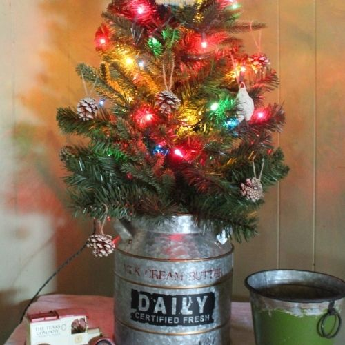 a christmas tree with a milk can for a stand
