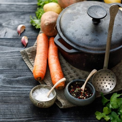 a cast iron pot with vegetables and spices