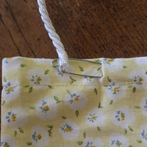 using a pin to pull cord through the channel of drawstring sewing kits