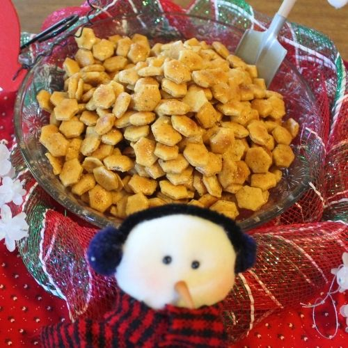 a bowl of seasoned oyster crackers with snowman decoration