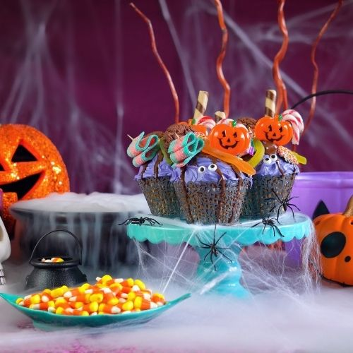 a table filled with Halloween cupcakes, candy corn, pumpkins and streamers