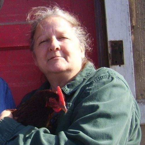 a woman in a green shirt holding a chicken