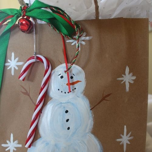 a brown paper bag painted with a snowman for gift wrapping