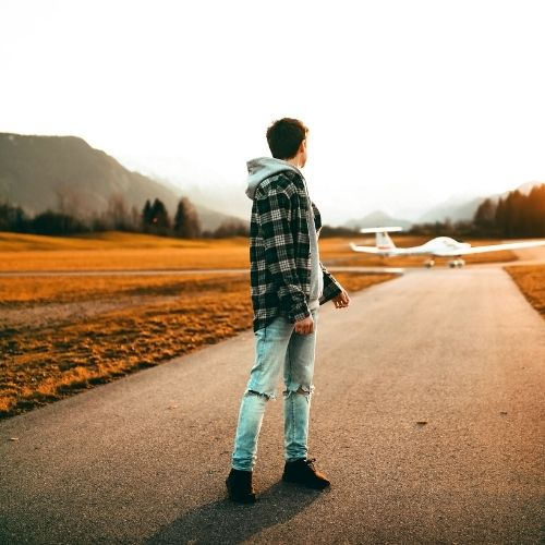 a young man looking back at a plane that is departing