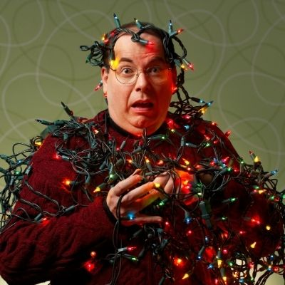 a man tangled up in Christmas lights