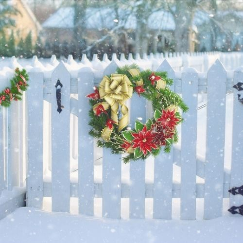 a Christmas wreath hung on a white picket fence