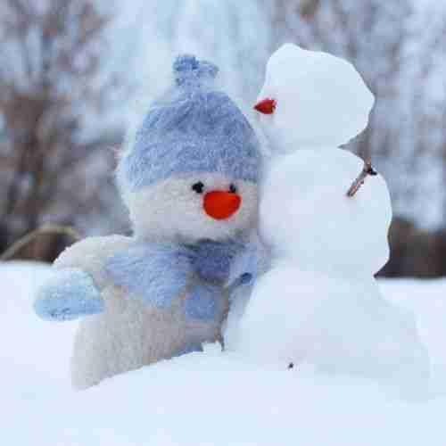 a stuffed snowman hugging a true snowman