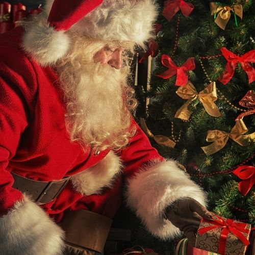 santa claus leaving gifts under a tree