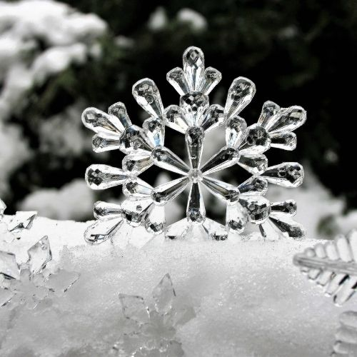 a glass snowflake embedded in a pile of snow