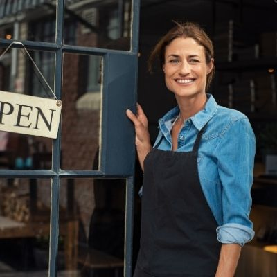 a small business woman welcoming customers to her shop