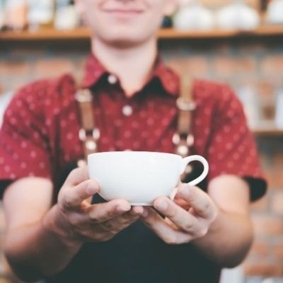 a small business owner handing a cup of coffee to a customer