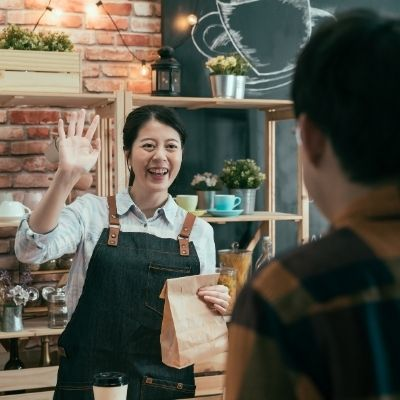 a small business shop owner waving to a customer