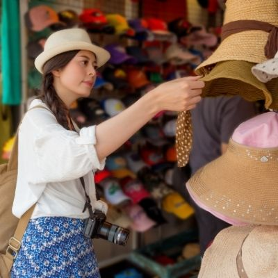 a tourist shopping for a hat at small businesses
