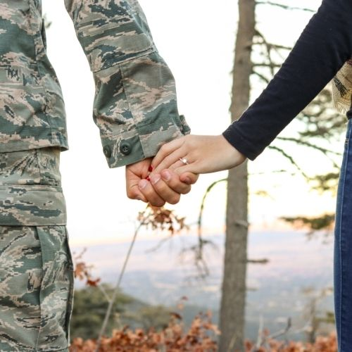 a military man holding his wife's hand