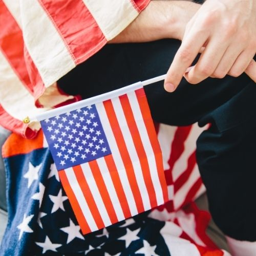 a hand holding a small American Flag