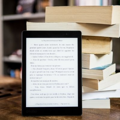 a digital ebook leaning against a stack of books