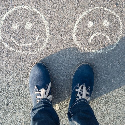 two feet with a happy face by one and a sad face by the other